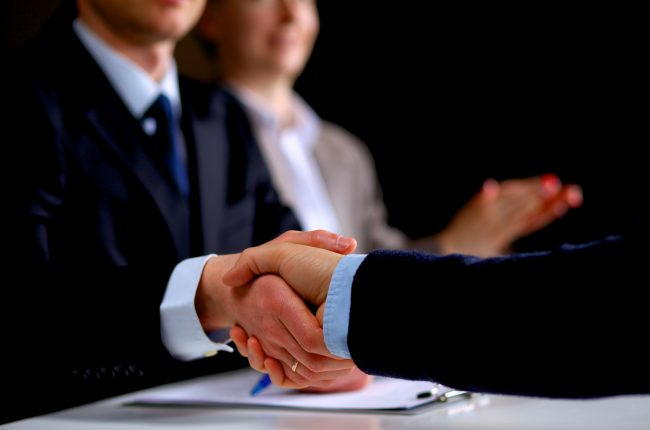 Business people shaking hands, finishing up a meeting .